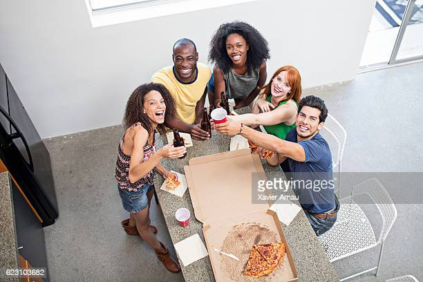 Friends enjoying with beers and pizza