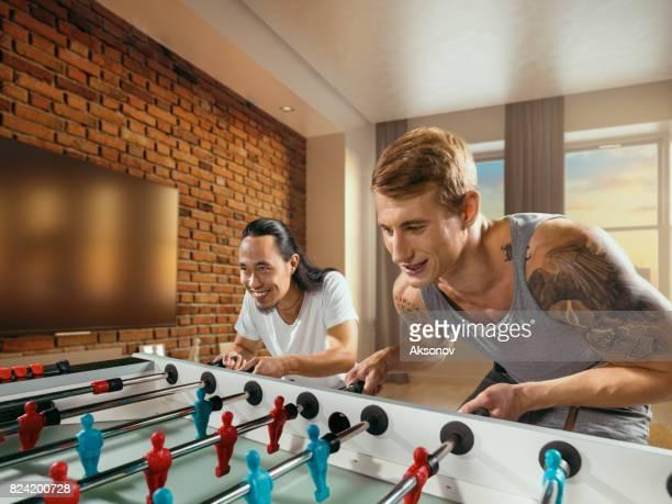 Amis avec enthousiasme le jeu table football/kicker