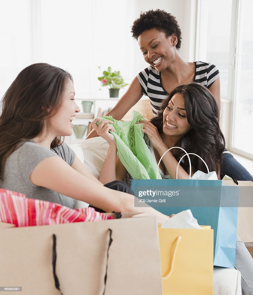 Friends examining shopping purchases : Stock Photo
