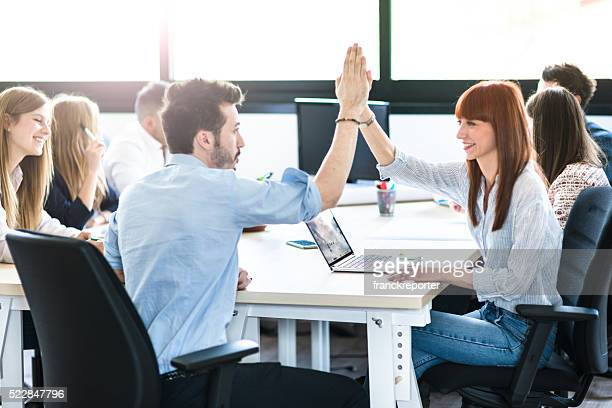 friends exchanging the highfive in the office