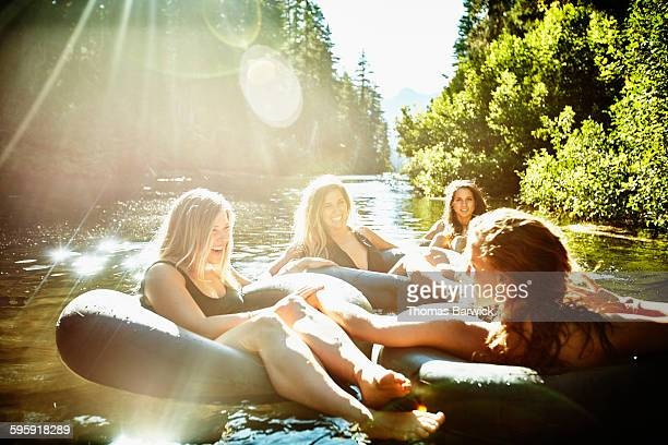 Friends floating on river on summer afternoon