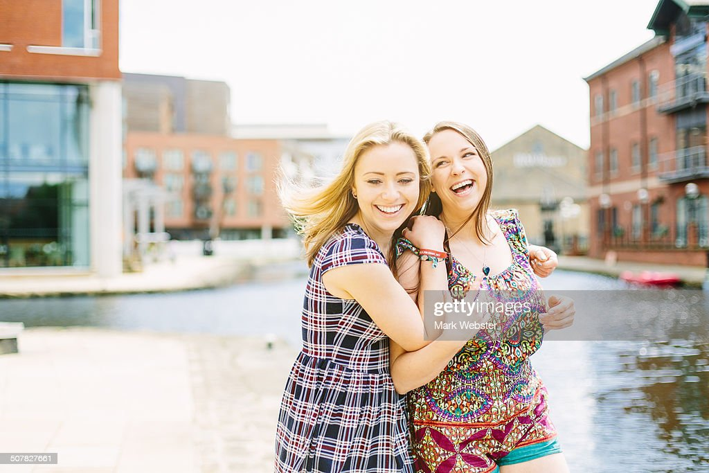 Friends fooling around by canal, Leeds, England : Stock Photo
