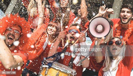 Amigos partidario los aficionados al fútbol que anima con el fútbol viendo confeti coinciden con eventos en el estadio - grupo de jóvenes con camisetas rojas que excitó la diversión en concepto de Campeonato del mundo de deporte : Foto de stock
