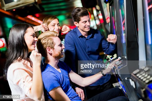 Friends gambling in a casino playing slot and various machines : Stock Photo