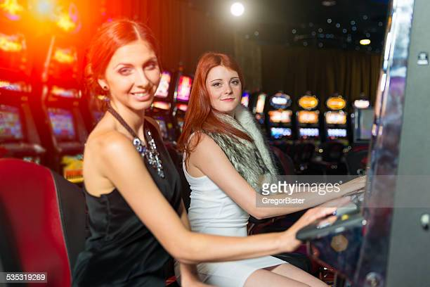 Friends gambling in the casino on slot machines