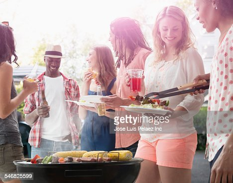 Friends grilling food at barbecue outdoors