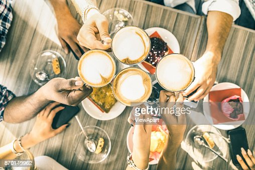 Friends group drinking cappuccino at coffee bar restaurant - People hands toasting at fashion cafeteria with upper view point - Winter drinks concept with men and women at cafe - Warm vintage filter : Stock Photo