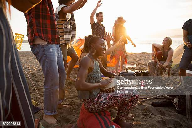 Friends hanging out and playing drums on beach