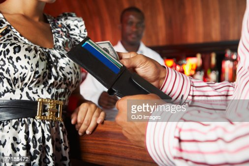 Friends hanging out at a club paying for something : Stock Photo