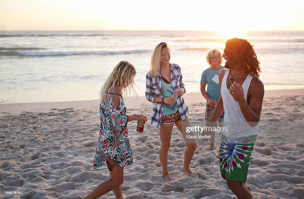 Friends hanging out at the beach in the sunset : Stock Photo