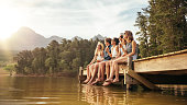 Portrait of relaxed young people sitting on the jetty with beers. Friends hanging out at the lake on a summer day.