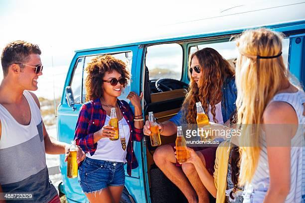 Amigos com uma cerveja perto de caravanas de van