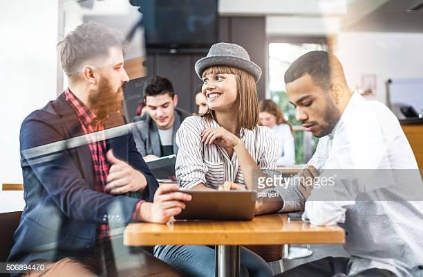 Freunde haben eine Kaffeepause und verwenden digitale tablet