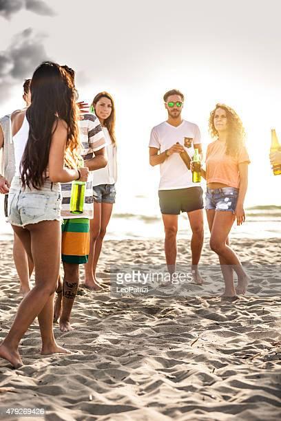 Amigos, tendo uma Festa na praia no anoitecer