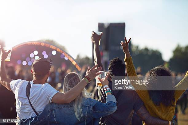 Friends having arms in the air in front of stage