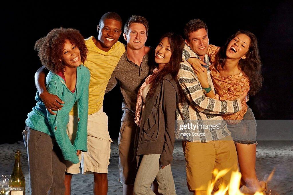 Friends having beach party at night : Stock Photo