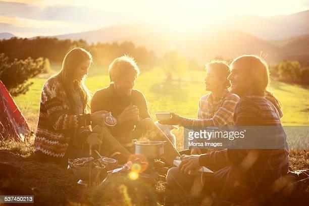 Friends having breakfast at campsite