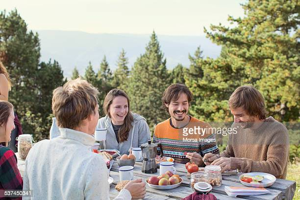 Friends having breakfast at picnic table