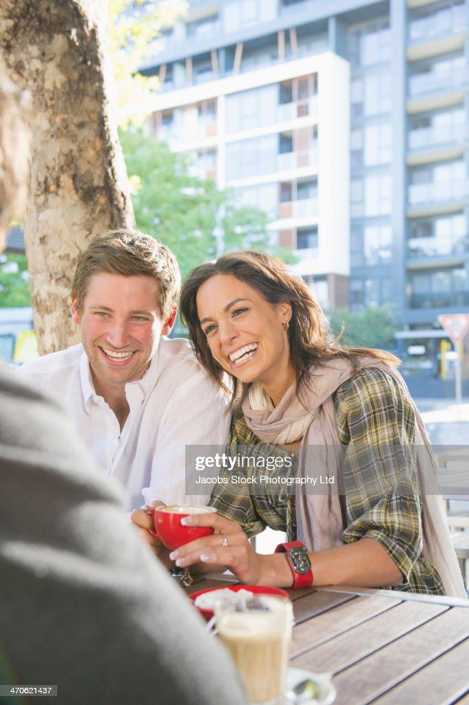 Friends having coffee at sidewalk cafe : Stock Photo