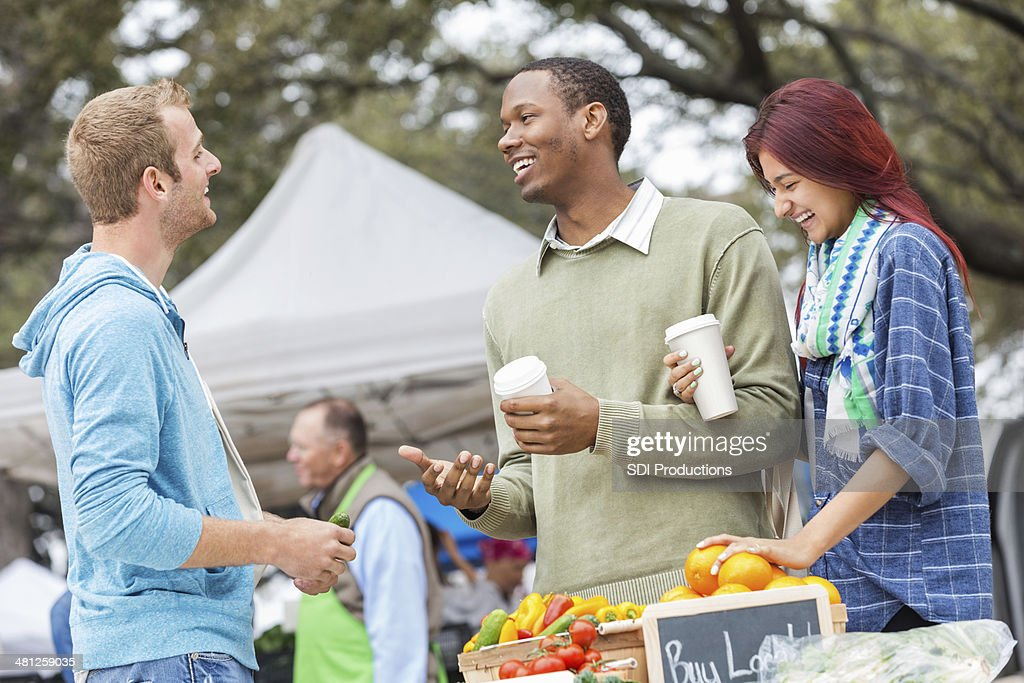 Friends having coffee together at outdoor farmers market