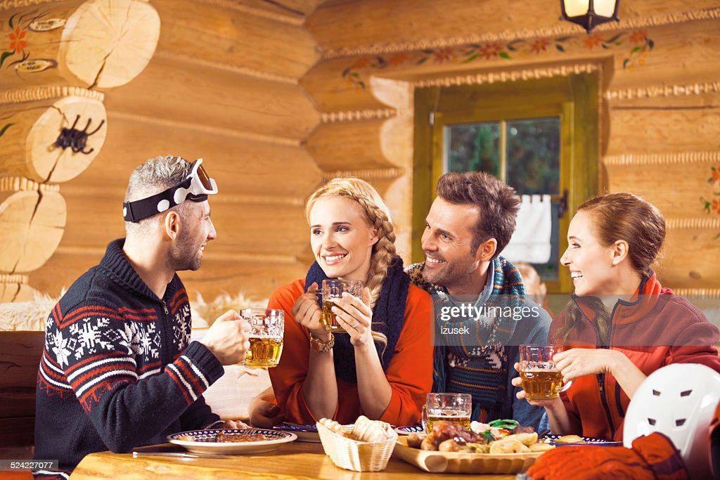 Friends having dinner in restaurant after skiing : Stock Photo