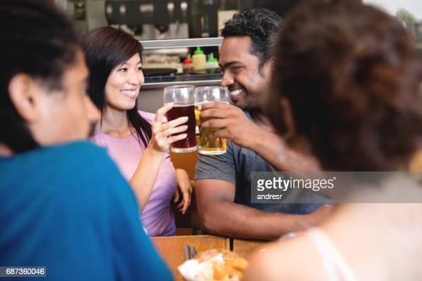 Friends having drinks and toasting at the bar