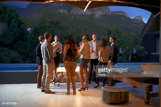 Friends having drinks by fireplace at poolside