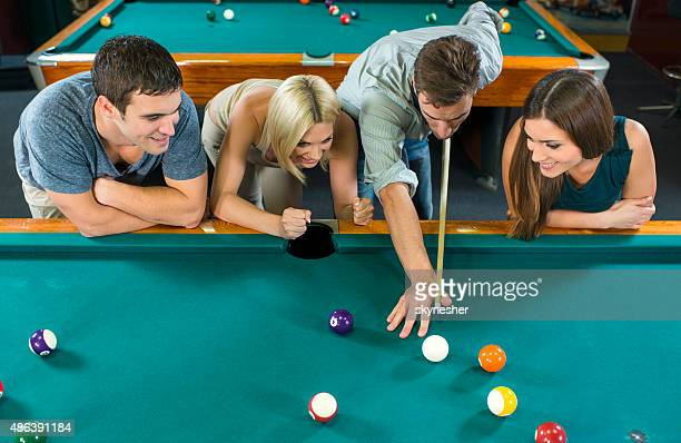 Friends having fun and playing billiard.