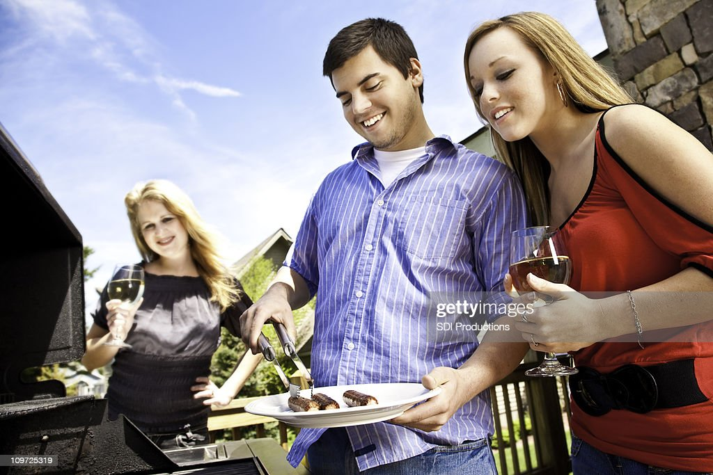 Friends Having Fun Cooking Hot Dogs on House Patio Grill : Stock Photo