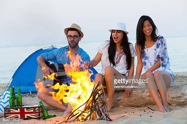 Amigos divirtiéndose cerca de la hoguera y campamento en la playa