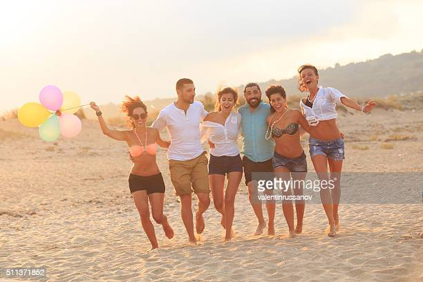 Friends having fun on beach with baloons at sunset