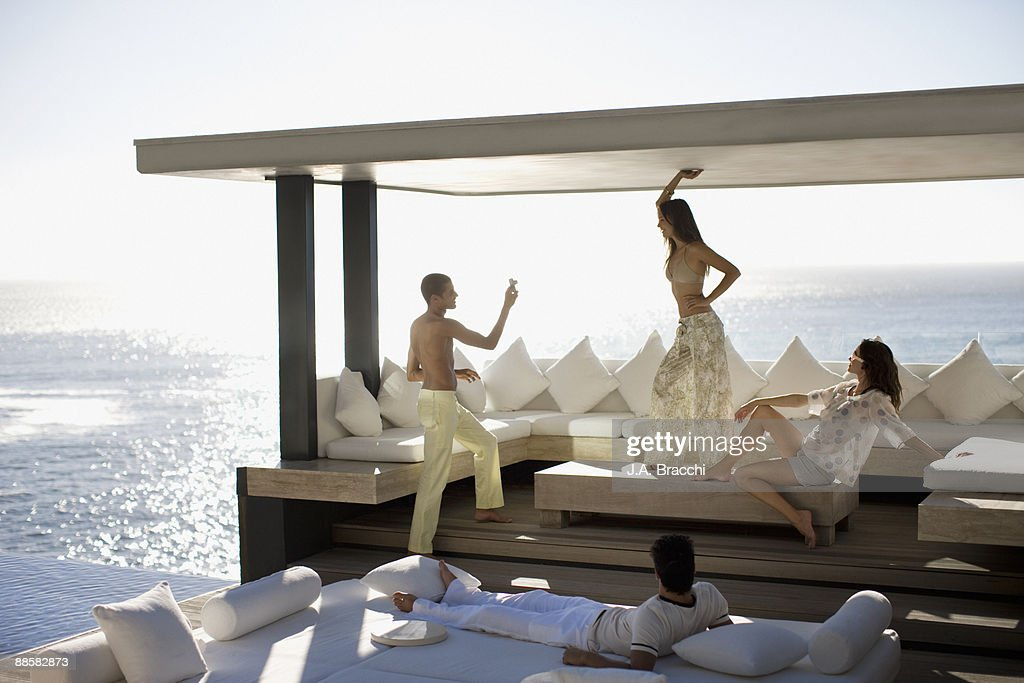 Friends having fun on patio near ocean : Stock Photo