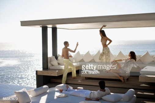 Friends having fun on patio near ocean : Stock Photo