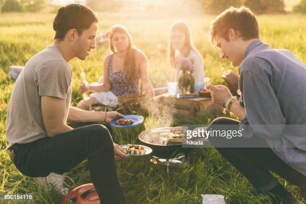Friends having fun on picnic with barbecue
