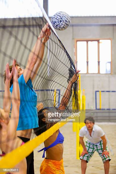 Friends having fun playing indoor beach volleyball