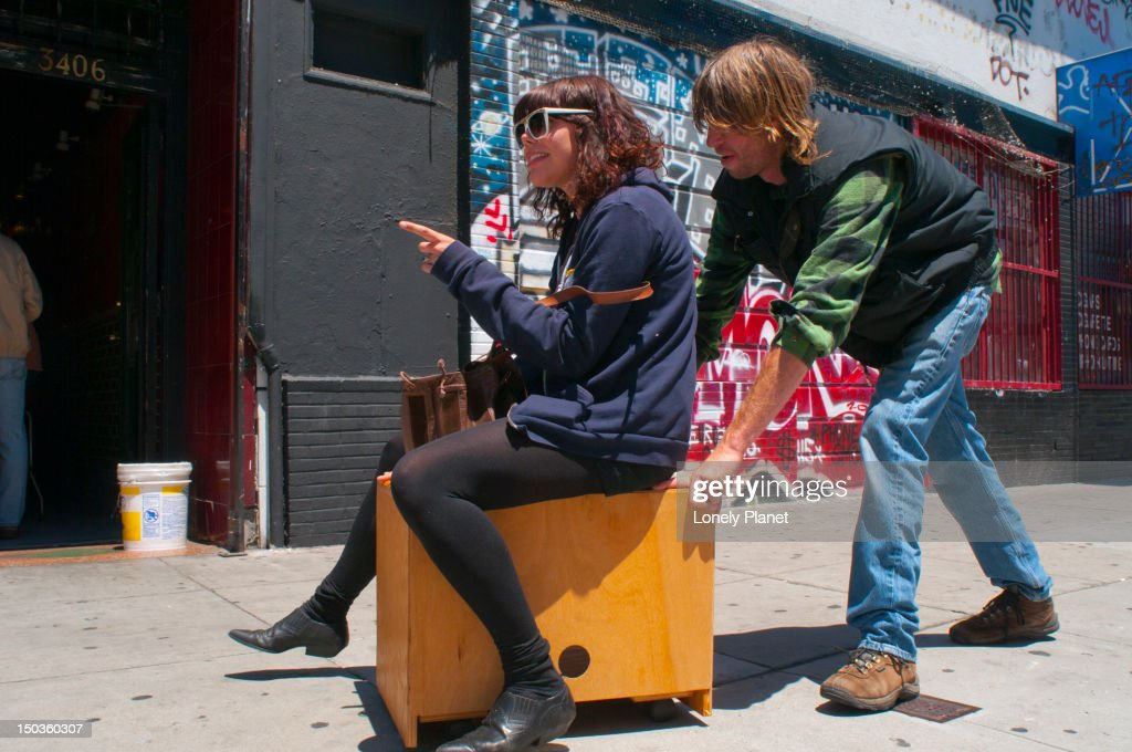 Friends having fun pushing each other through the Mission District on piece of furniture.
