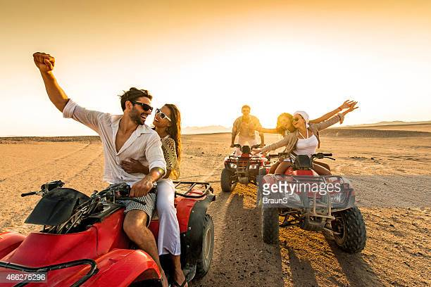 Friends having fun riding quad bikes in desert