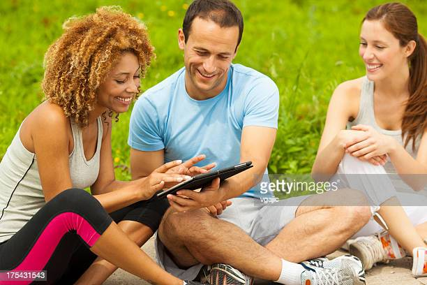 Friends Having Fun with digital tablet outdoors.