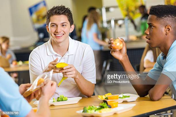 Friends having healthy lunch together in high school cafeteria