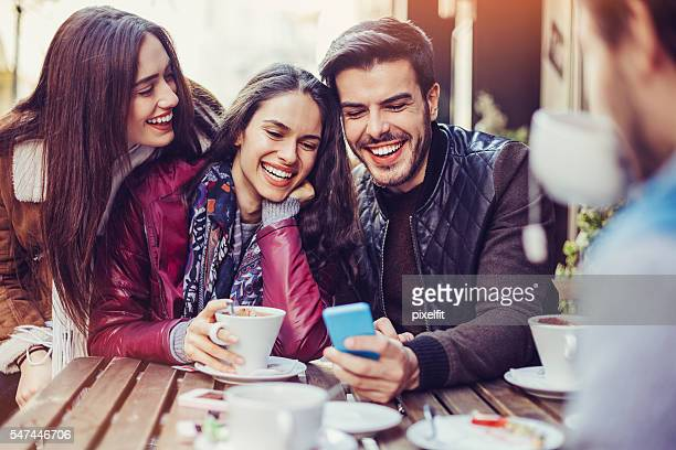 Friends having hot drinks and looking at smart phone