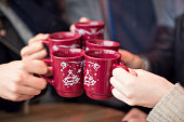 Close up of hands holding cups with hot wine at outdoor cafe on a street, christmas market. Cups are decorated with christmas tree ornament. Vienna, Austria.