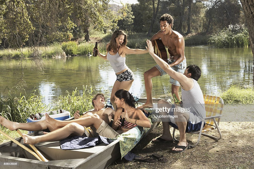 Friends having party beside lake : Stock Photo