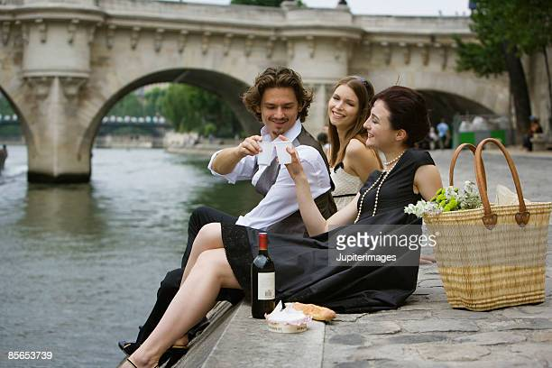 Friends having picnic , River Seine , Paris , France