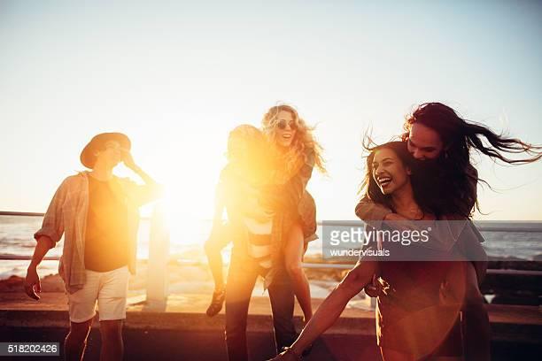 Amici avendo Portare a cavalluccio passeggiate sulla spiaggia al tramonto