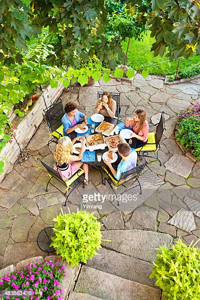 Friends Having Pizza Dinner in Outdoor Background Patio