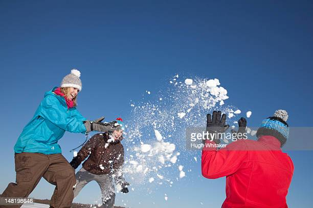Friends having snowball fight outdoors