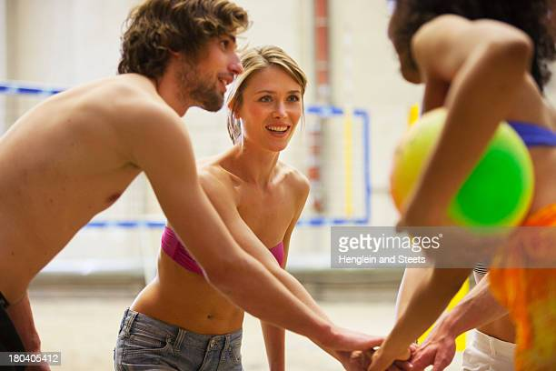 Friends having team talk at indoor beach volleyball