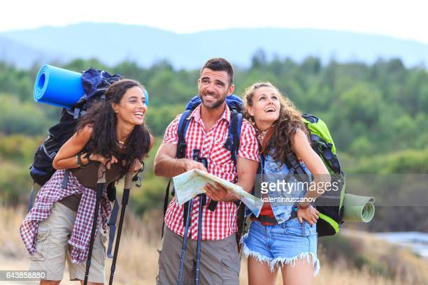 Friends hiking in nature and using a map