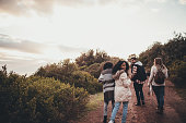 Friends hiking in nature. Group of man and women walking along the countryside road. Woman turning around and looking at camera.