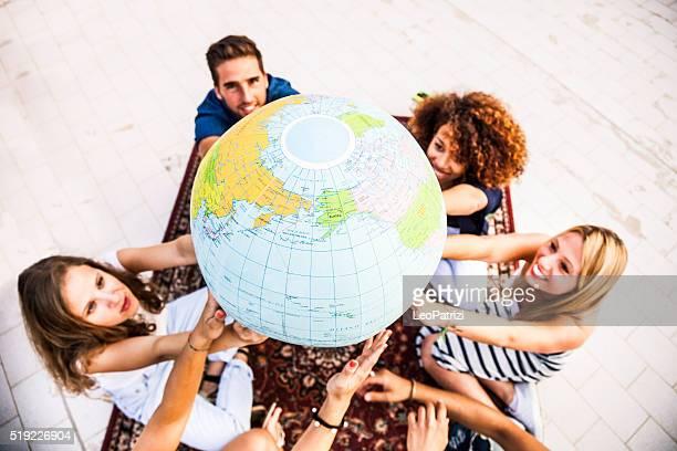 Amigos sosteniendo y mirando globo de tierra